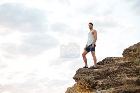 Young casual man standing on the mountain rock