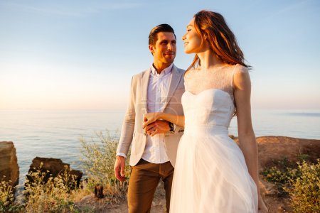 Attractive bride and groom getting married by the beach