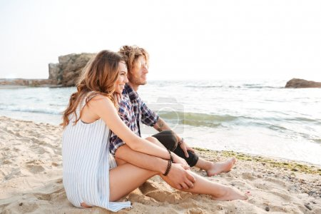 Couple sitting on the beach in summer