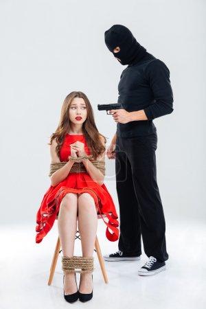 Photo pour Homme criminel à balaclava permanent et menace avec arme à feu pour femme assise délimitée avec des cordes - image libre de droit