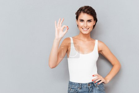 Full length portrait of a cheerful girl showing ok sign