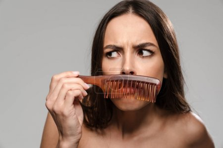 Pretty young girl posing with comb like with moustache isolated on gray background
