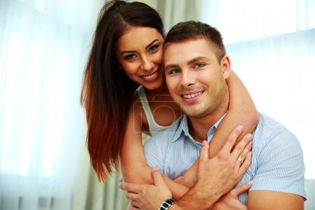 Photo for Smiling young couple hugging at home - Royalty Free Image