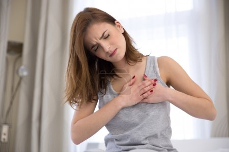 Young woman in pajamas having heart attack...