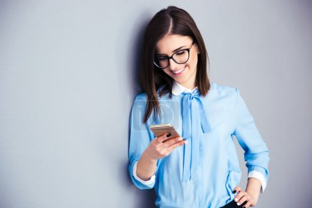 Happy businesswoman using smartphone