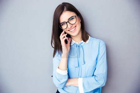 Photo for Happy businesswoman talking on the phone over gray background. Wearing in blue shirt and glasses. Looking at camera - Royalty Free Image