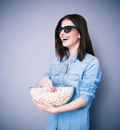 Lauhging woman in cinema glasses holding bowl with popcorn