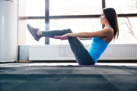 Happy young woman doing exercise on yoga mat