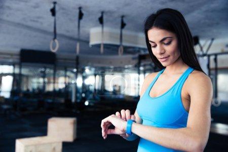 Photo pour Heureuse jeune femme à l'aide de traqueur d'activité dans la salle de fitness - image libre de droit
