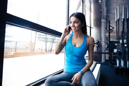 Smiling fit woman talking on the phone