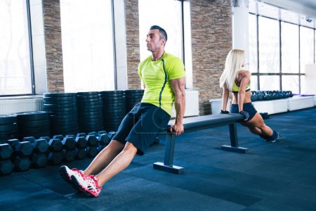Woman and man workout with hands on bench