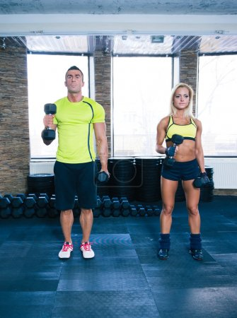 Woman and man working out with dumbbells