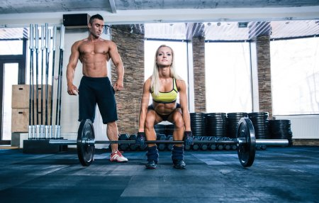 Woman workout with barbell and coach