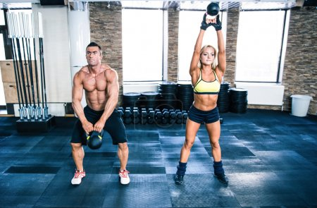 Photo for Muscular man and fit woman workout with kettle ball at gym - Royalty Free Image