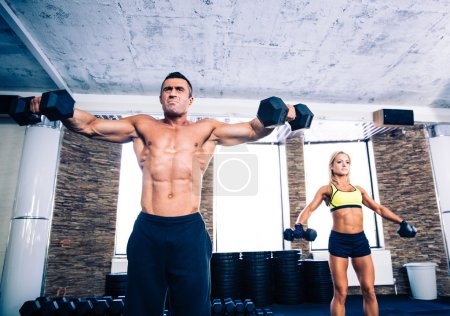 Photo for Muscular man and fit woman lifting dumbbells at gym - Royalty Free Image