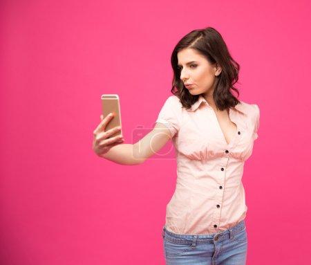 Photo pour Jeune femme faisant selfie photo sur smartphone sur fond rose - image libre de droit
