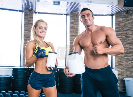 Muscular man and sporty woman holding container wi...