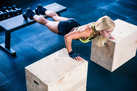Beautiful sports woman doing push ups on fit box