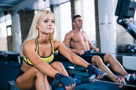 Man and woman workout on training simulator