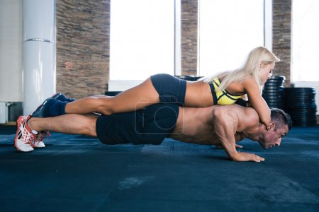 Muscular man doing push ups with woman on back