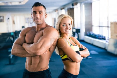 Muscular man and sporty woman standing in gym
