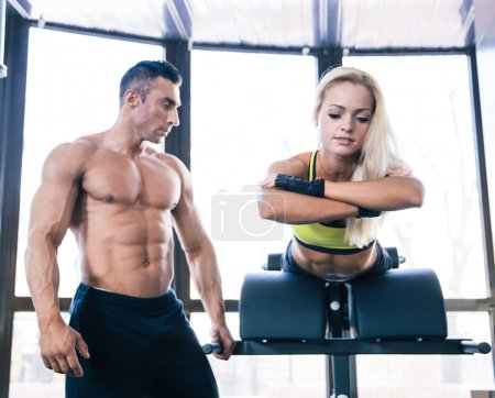Photo for Spoty woman flexing back muscles on bench with muscular coach in gym - Royalty Free Image