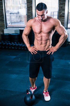 Muscular man reading for workout with kettle ball