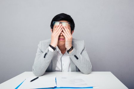 Young asian businessman rubbing his eyes