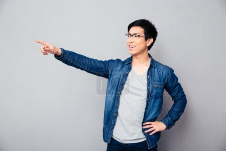 Smiling asian man showing finger away