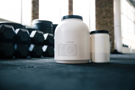 Plastic containers with sports nutrition on dumbbells