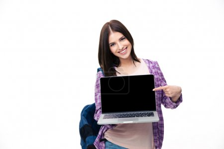 Photo for Happy young woman showing finger on laptop screen over white background. Looking at camera - Royalty Free Image