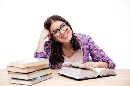 Photo pour Heureuse étudiante assise à la table avec un livre sur fond blanc et regardant la caméra - image libre de droit