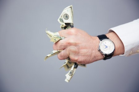 Businessman hand holding bills of US dollar in fist