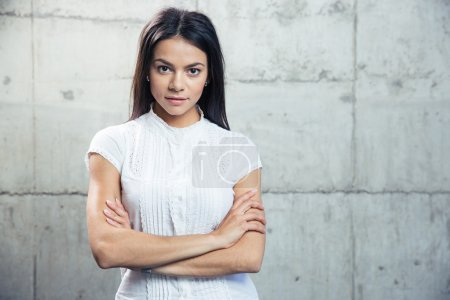 Photo for Portrait of a happy businesswoman standing with arms folded over concrete wall and looking at camera - Royalty Free Image