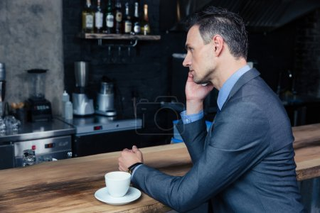 Thoughtful businessman talking on the phone in cafe