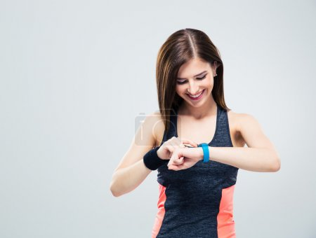 Happy young woman using activity tracker