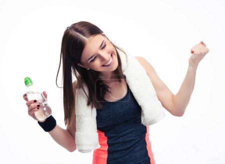 Photo pour Joyeux fitness femme avec towe et bouteille d'eau célébrant sa victoire isolée sur un fond blanc. Regardant la caméra - image libre de droit