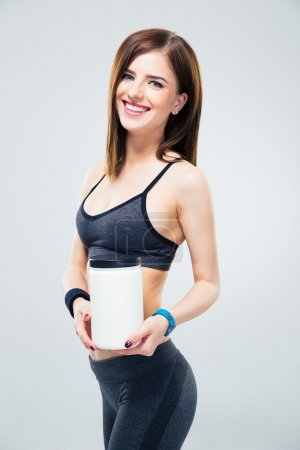 Smiling fitness woman holding jar of protein