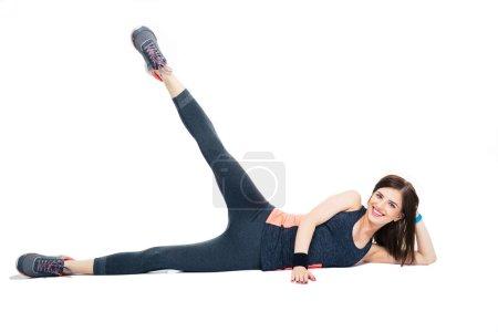 Photo pour Heureuse femme sportive faisant de l'exercice d'étirement isolé sur un backgorund blanc. Regardant la caméra - image libre de droit