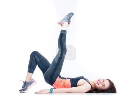 Photo pour Femme heureuse couchée sur le sol et étirant les jambes isolées sur un fond blanc. Regardant la caméra - image libre de droit