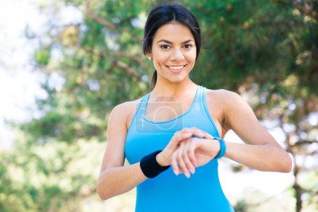 Photo pour Sourire femme sportive en utilisant la montre intelligente à l'extérieur et en regardant la caméra - image libre de droit