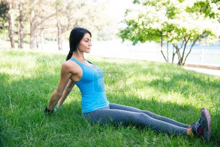Fitness woman doing stretching exercsises in park