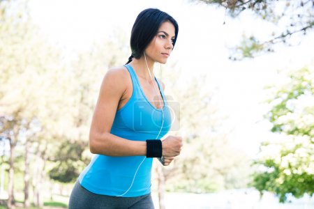 Charming sporty woman running in park