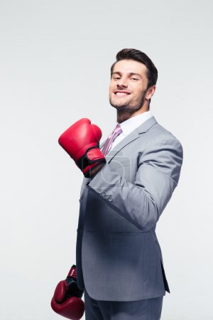 Photo for Smiling businessman in boxing gloves over gray background. Looking at camera - Royalty Free Image