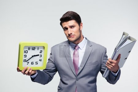 Unhappy businessman holding folders and clock