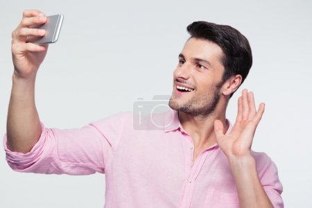 Happy businessman showing greeting sign on smartphone