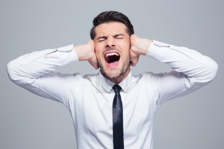 Businessman covering his ears and screaming