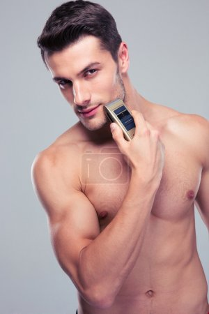 Muscular man shaving with electric razor