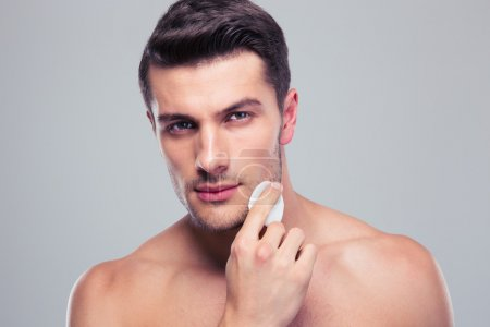 Man cleaning face skin with batting cotton pads