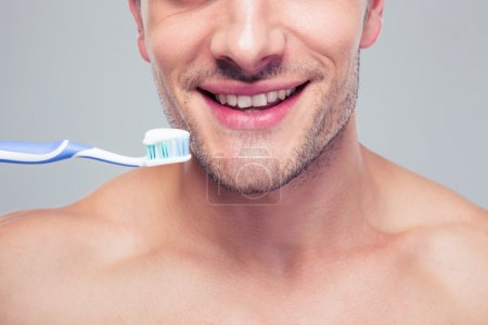 Happy man holding toothbrush
